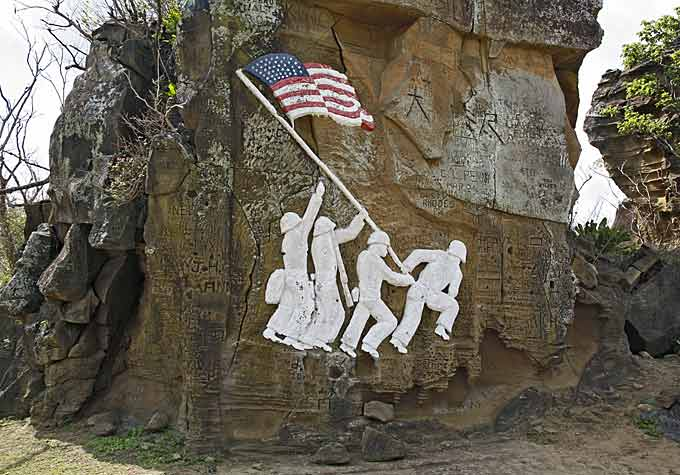 Carved sandstone flag raising sculpture